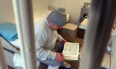 Homem na cadeia lendo a Bíblia